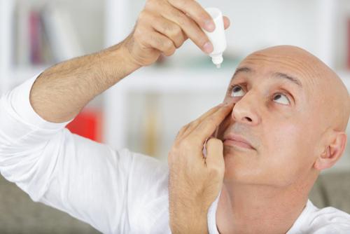 Man putting drops in eyes