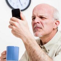Man squinting reading phone