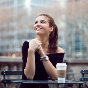 Hopeful woman drinking coffee